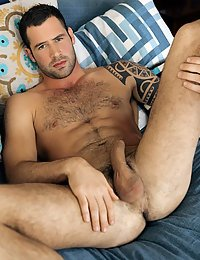 He's a really cute hairy guy with a big cock